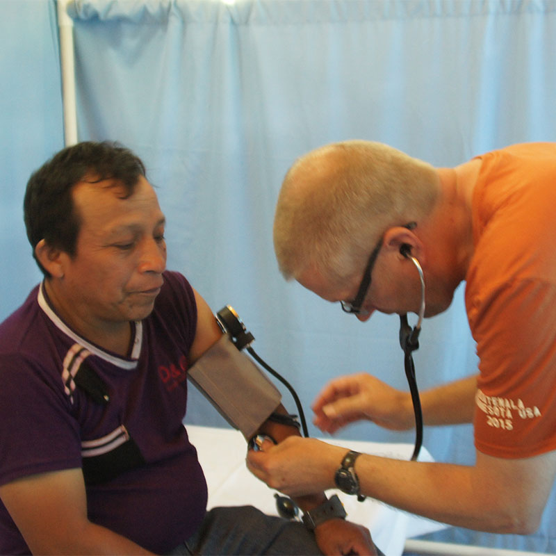 Dr. Haugen checks a patient's blood pressure in a clinic in Guatemala.