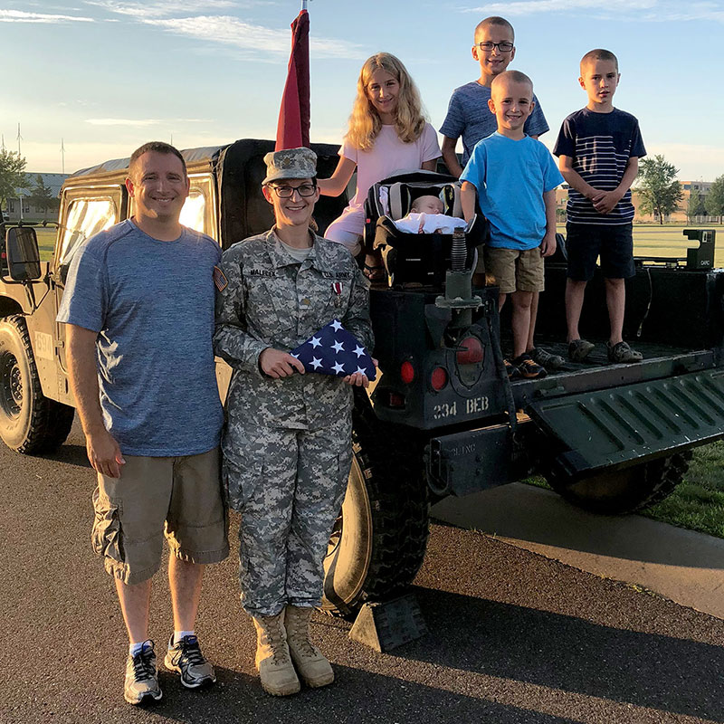 Terri with husband and children holding her U.S. flag