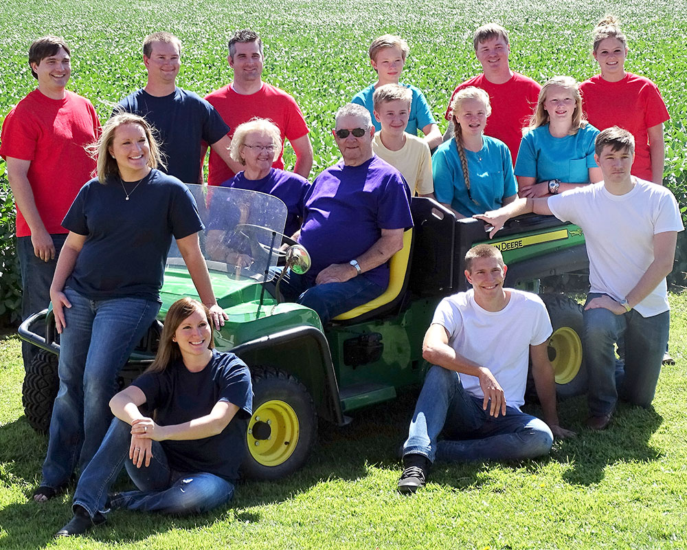 Group of people gathered on a tractor in front of a field