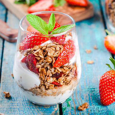 Strawberry topped granola parfait in a glass